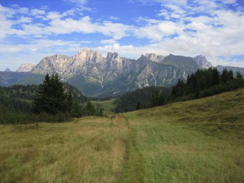 widok z Col dei Baldi na przeł. Pecol (1786 m - biała nitka szutrowej drogi), za nią dol. Fiorentina (w dole, niewidoczna), za którą grupa M. Cernera (2657 m) #góry #Dolomity #Włochy
